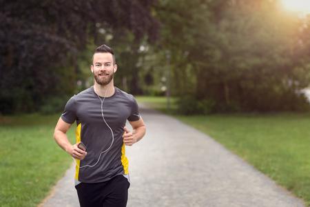 上半身のコピー スペースとカメラに近づいて、彼の携帯電話で音楽を聞いて公園をジョギングしていたフィットのひげを生やした若い男
