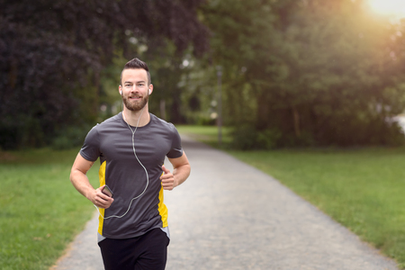 Fit bearded young man jogging through a park listening to music on his mobile phone, upper body approaching the camera with copy space Banque d'images