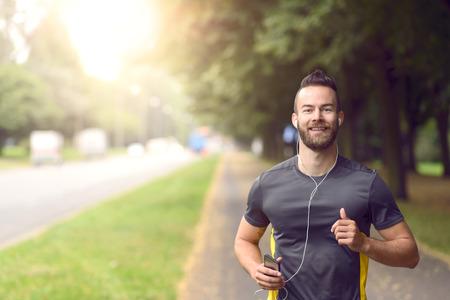 фитнес: Человек бег трусцой вдоль деревьев вдоль тротуара на оживленной дороге приближается к камере в концепции фитнес и активный образ жизни