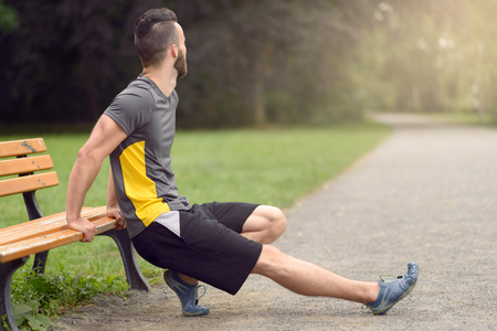 turn away: Young man doing stretching exercises on a wooden park bench resting on his hands with leg extended looking away from the camera down the path, healthy lifestyle concept with copy space