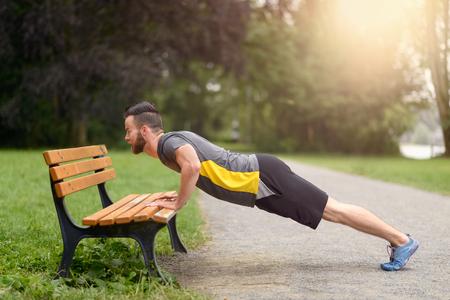 Jongeman werken doet push-ups op een houten bankje in het park toen hij opwarmt voor zijn dagelijkse training of jog