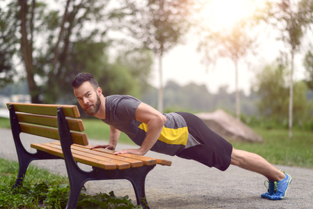 body toning: Young man working out doing push-ups on a wooden park bench as he warms up for his daily workout or jog