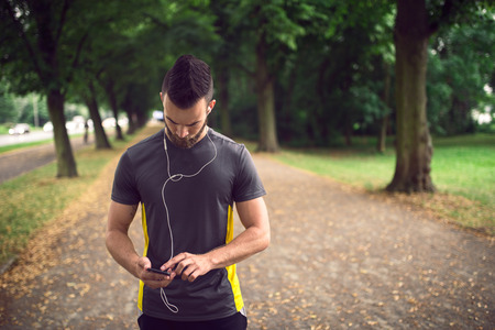 outdoor fitness: Attractive bearded man listening to music on his mobile phone as he stands in a tree lined avenue in a park looking at the camera with a smile