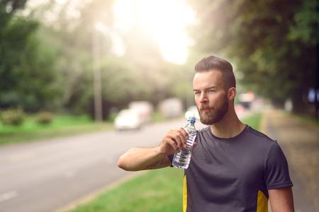 tomando agua: Hombre joven con una barba beber agua embotellada mientras camina por una avenida arbolada en un parque, cerca cabeza y hombros