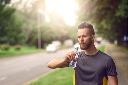 bottled: Young man with a beard drinking bottled water as he walks down a tree lined avenue in a park, close up head and shoulders Stock Photo