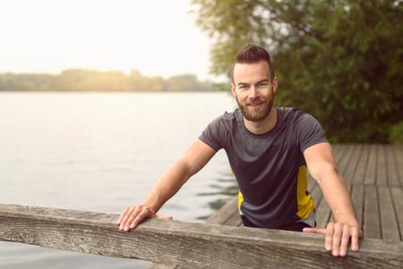 Jonge man doen rekoefeningen op een houten terras met uitzicht op het meer terwijl hij lacht naar de camera in een gezonde leefstijl concept