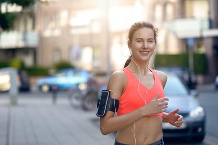 Fit jonge vrouw joggen langs een stedelijke straat naderen van de camera met haar lange haren vliegen en een gelukkige glimlach, zon flare achter en kopieer ruimte