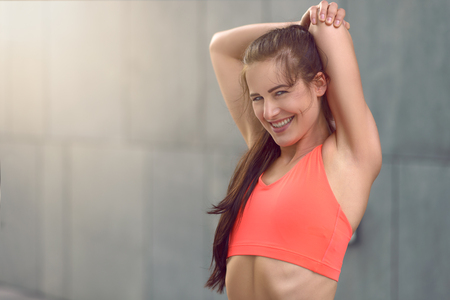 arms above head: Fit athletic young woman with a happy smile stretching her arms above her head in her sportswear outdoors near a gre< wall with copy space Stock Photo
