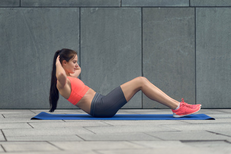body torso: Athletic young woman working out in the courtyard of a commercial building on her yoga mat doing crunches