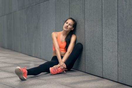 ropa deportiva: Atlético joven sentado en pavimentos de hormigón apoyada contra una pared sonriendo en silencio a la cámara en ropa deportiva de moda