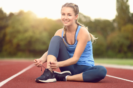 sports track: Sporty young woman sitting on a race track at a sports stadium smiling as she ties her laces on her running shoes backlit by the glow of the morning sun Stock Photo
