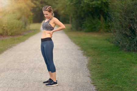 slipped: Woman athlete pausing to relieve her back pain holding her hand to her lower back with a grimace while out training in the countryside with copyspace Stock Photo
