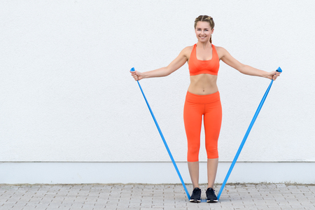 Young sporty woman doing core strengthening exercises using latex bands in a health and lifestyle concept, smiling at the camera Фото со стока