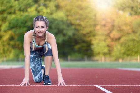 agachado: Mujer joven atlética en la posición de arranque se puso en cuclillas en un carril en una pista de carreras mirando a la cámara con una sonrisa, con copia espacio Foto de archivo