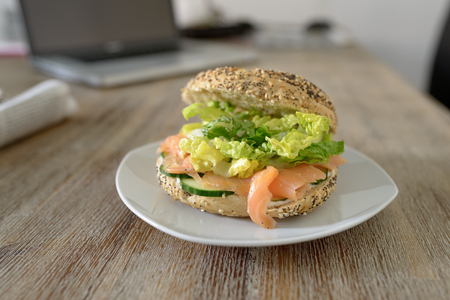 Deliciously prepared wholewheat bagel with smoked salmon, lettuce and cucumber slices on a table with an open laptop in the background Stock Photo