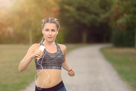 mp3 player: Woman listening to music on her earplugs and MP3 player while jogging along a country road in a healthy lifestyle, exercise and fitness concept Stock Photo