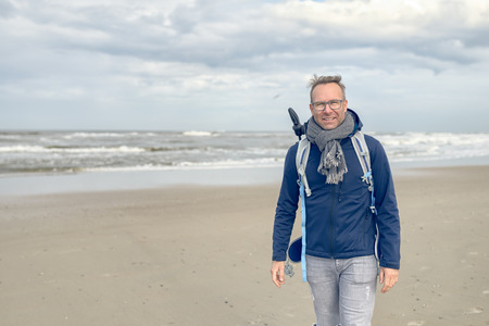 blustery: Middle-aged man wearing glasses, a backpack and a scarf walking along a cold blustery beach on a rainy overcast autumn or winter day, with copy space