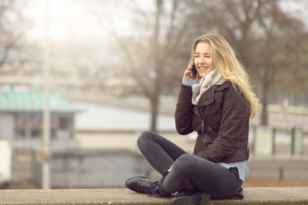 Pretty trendy young woman or student chatting on her mobile phone as she sits cross legged on a wall outdoors on a cold winter day