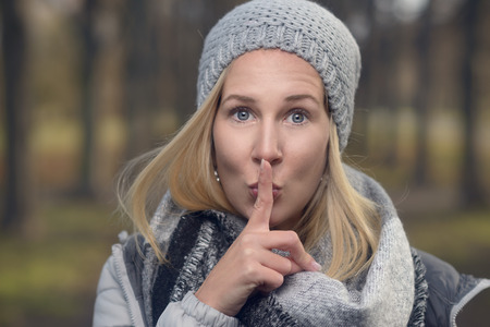 Attractive woman in warm stylish winter fashion standing outdoors in a forest making a shushing gesture raising her finger to her lips as she requests silence or secrecy