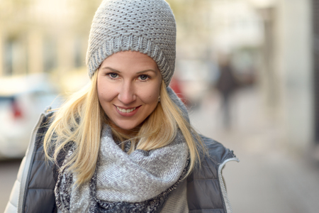 warm jacket: Smiling attractive friendly young woman in a stylish grey winter outfit with knitted cap and scarf and warm jacket in an urban street Stock Photo