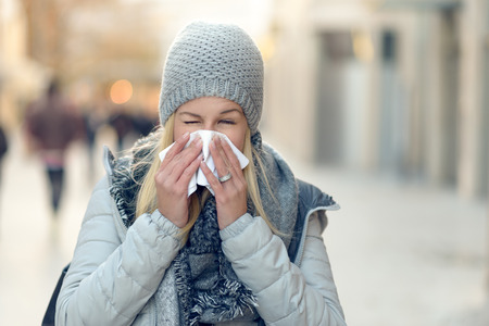 handkerchief: Woman with a seasonal winter cold blowing her nose on a handkerchief or tissue as she walks down an urban street in a health and medical concept Stock Photo