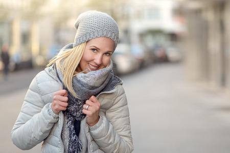 Lächelnde attraktive freundliche junge Frau in einem stilvollen grauen Winter-Outfit mit gestrickte Mütze und Schal und warme Jacke in einer städtischen Straße