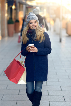 Gorgeous young woman out Christmas shopping in a knitted winter cap smiling happily as she glances behind her while walking in an urban street Фото со стока