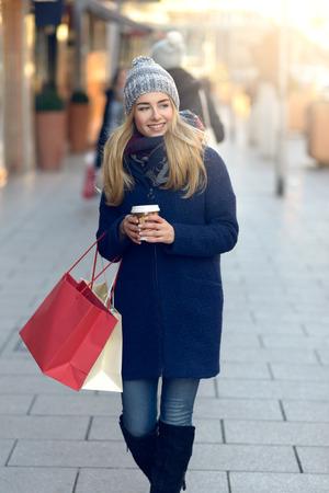 Schitterende jonge vrouw uit kerstinkopen in een gebreide winter cap gelukkig glimlacht als ze kijkt achter haar tijdens het wandelen in een stedelijke straat Stockfoto