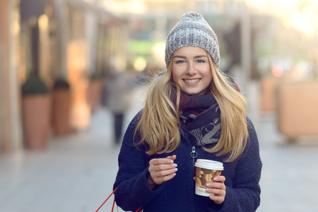 Gorgeous young woman out Christmas shopping in a knitted winter cap smiling happily as she glances behind her while walking in an urban street Stock Photo