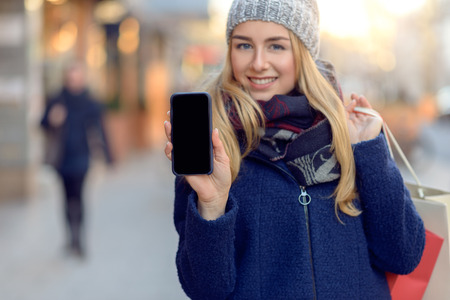 warmly: Pretty young woman holding up her mobile phone with a blank display as she stands on an urban street in winter warmly dressed in a knitted woollen scarf, hat and jacket