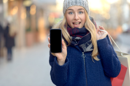 warmly: Pretty young woman holding up her mobile phone with a blank display as she stands on an urban street in winter warmly dressed in a knitted woollen scarf, hat and jacket with an excited expression