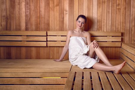 Side view full length portrait of young woman smiling sitting on wooden sofa bench in sauna wrapped in white towel, with hair in donut bun