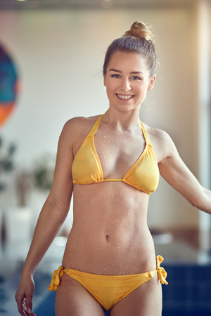 Beautiful young sporty woman standing in swimming pool in yellow two-piece swimsuit, looking away and smiling
