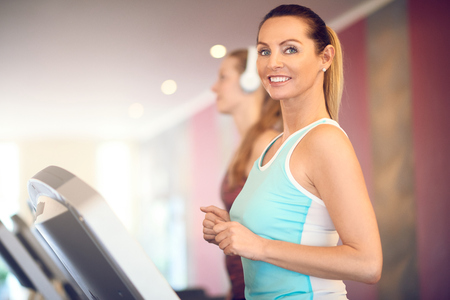 mujer deportista: Atractiva mujer de mediana edad en una tapa de menta de pie en la cinta de correr en el gimnasio, mirando a cámara y sonriendo con copia espacio