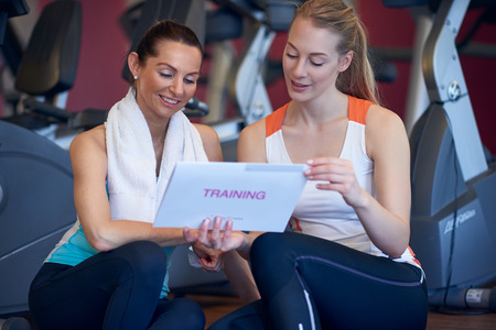Attractive fit young female athlete with her personal trainer holding their training plan conceptual of planning and strategy before success and achievement