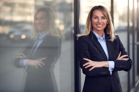 Single selbstbewusste und attraktive weibliche Geschäftsfrau in blauen Anzug mit Grinsen lehnt auf Fenster im Freien