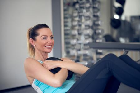forme et sante: Paire de jeunes femmes adultes faisant des exercices de torsion russes musculaires abdominaux tout en tenant des poids