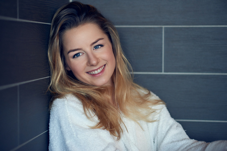 Pretty young blond woman with a happy sincere smile leaning back into the corner on a grey tiled wall with folded arms looking to the side with copy space alongside Stok Fotoğraf