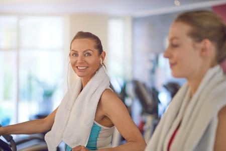 선택적 포커스가있는 두 번째 여자 지나서보기에서 카메라를보고 장비에 체육관에서 친구와 함께 웃고 친절한 젊은 여자가 웃고