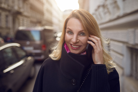 Pretty vivacious woman chatting on a mobile phone as she walks down a busy urban street smiling happily at the camera Stock Photo
