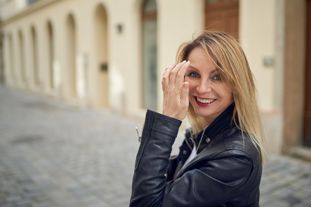 flicking: Attractive blond woman standing outdoors in a courtyard flicking her long blond hair off her face with her hand as she smiles at the camera