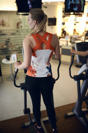 Rear view of young woman using anaerobic exercise machine in gym Stock fotó