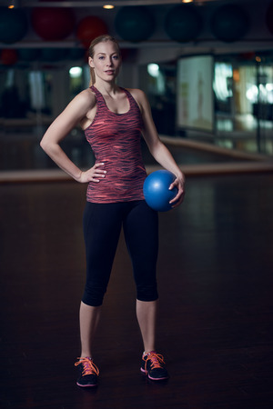 Full body portrait of fit woman in fitness studio with medicine ball