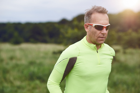 Middle-aged sporty man wearing sunglasses jogging in the countryside though grassland in a close up upper body view with copy space Stock Photo - 84075149