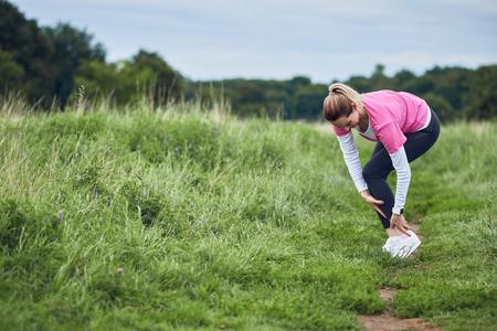 실외에서 달리면서 적당히 마모 된 운동 여성은 부상당한 발목에 힘을 주어야합니다.