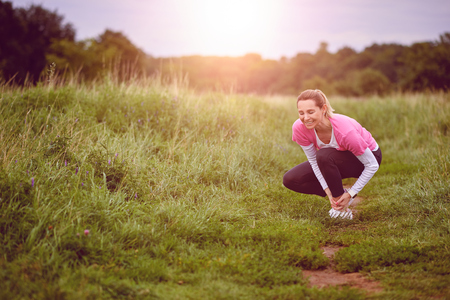 An exercising woman in fit wear while running outdoors, stop to clutch an injured ankle.