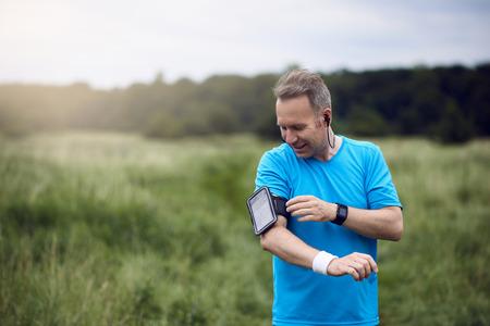 Lterer Mann mit Smartphone auf seinem Arm Musik hören, während im Freien stehen Standard-Bild - 84499723