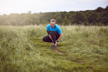 An exercising man in fit wear while running outdoors, stop to clutch an injured ankle.