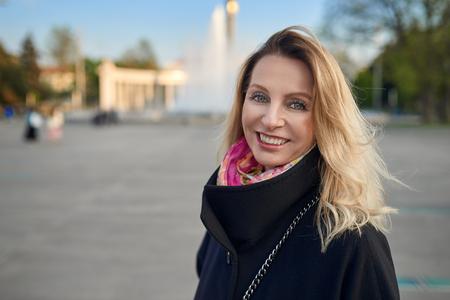 Outdoor portrait of mature blonde smiling woman in street Reklamní fotografie