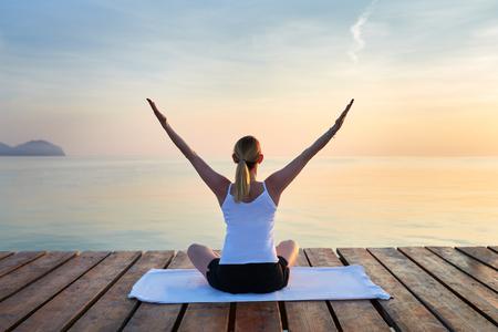 Achtermening van jonge die vrouw op handdoek het praktizeren yoga door overzees bij zonsondergang wordt gezeten Stockfoto